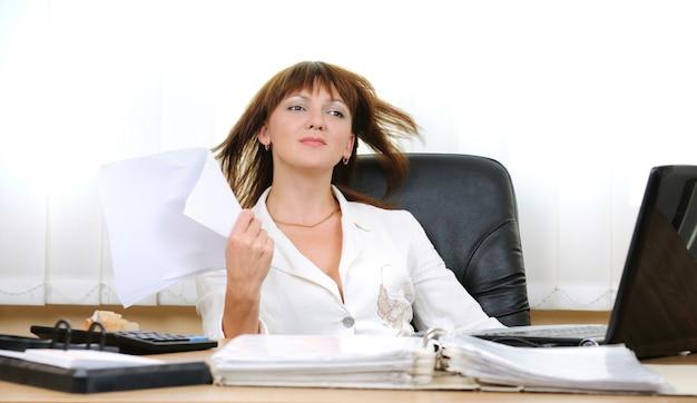 机に座ってスーツを着た疲れた白人白人女性がオフィスでファンとして紙シートを使用してリラックスします。ドキュメント、テーブル上のラップトップのフォルダ。