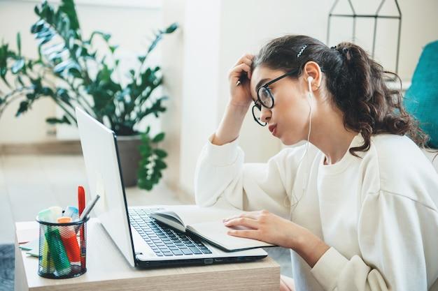 本を読んでイヤホンをつけながらコンピューターで勉強している疲れた白人女性