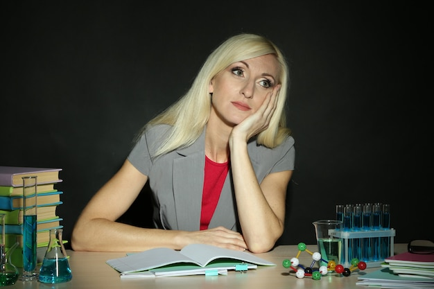 Tired chemistry teacher sitting at table on dark colorful
