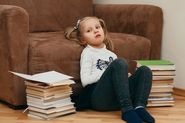 Tired child at home on a background of books