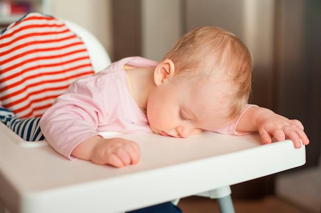 점심 식사 후 유아용 의자에서 자고 피곤한 아이. 식사와 잠을 통해 귀여운 딸