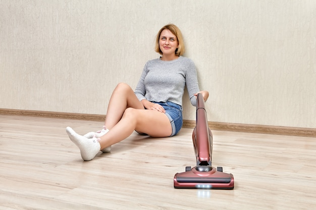 피곤한 청소부는 led 조명이 켜진 무선 스틱 진공 청소기의 도움으로 바닥에 앉아 진공 청소기로 청소하고 있습니다.