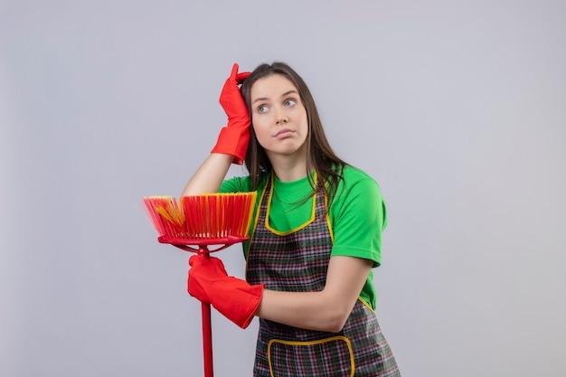 La ragazza stanca di pulizia che porta l'uniforme in guanti rossi che tengono la scopa mise la mano sulla testa sulla parete bianca isolata