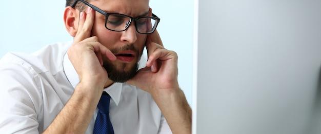 Усталый клерк в ноутбуке на рабочем месте в очках