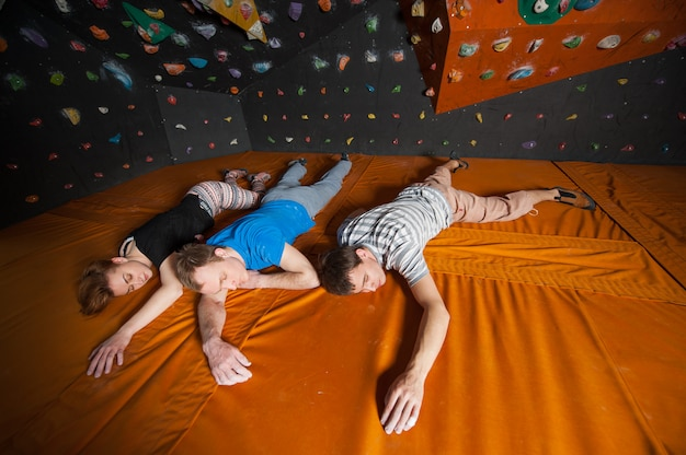 Tired climbers with closed eyes lying near rock wall indoors