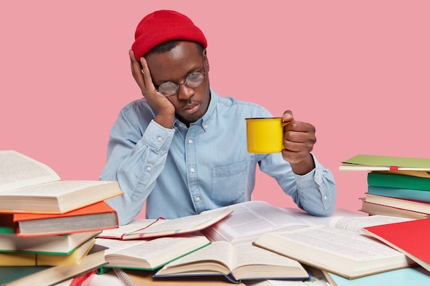 피곤하고 집중된 어두운 피부를 가진 남자는 심각한 표정을 지으며 뜨거운 음료 머그잔을 들고 있습니다.