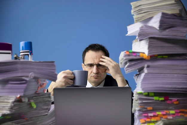 Tired concerned businessman holding cup of coffee at office desk with huge pile of documents