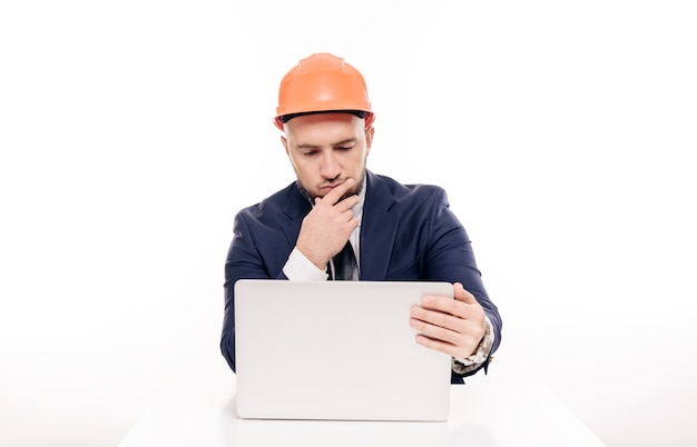 A tired constructor businessman in an orange helmet looks at the laptop screen and studies the construction project. sits at the table and drinks coffee, nervous