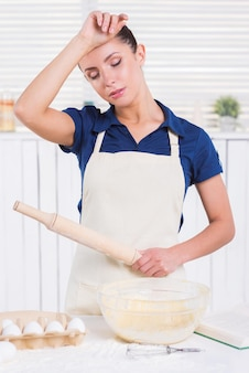 Tired of cooking. tired young woman in apron holding rolling pin and touching her forehead with hand while standing in a kitchen