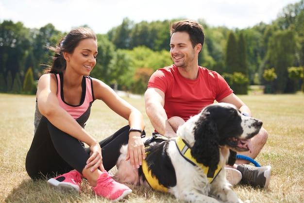 疲れたカップルと彼らの犬は激しい運動の後に休んでいます