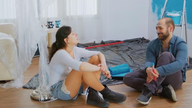 彼らのアパートの改修中に疲れたカップル。改装と改善中のアパートの改装と住宅建設。修理と装飾。