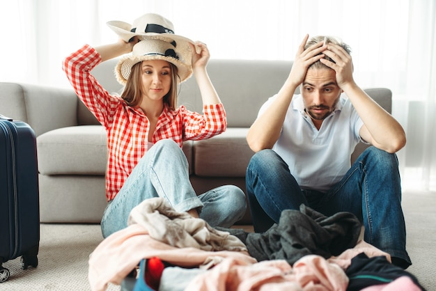 Tired couple packing overloaded bag for vacation
