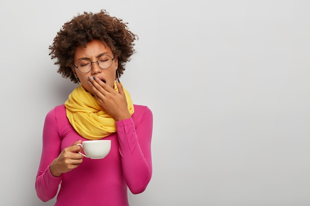 Усталая кудрявая женщина зевает, имеет сонное выражение лица, пьет кофе рано утром, держит белую кружку горячего напитка