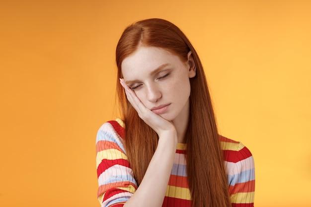 Усталая милая рыжая студентка измучена чувствовать сонливость засыпать стоя, наклонившись лицом ладонью, закрыть глаза, работая неполный рабочий день в ночную смену, мечтать не хватает энергии хочу спать кровать оранжевый фон.