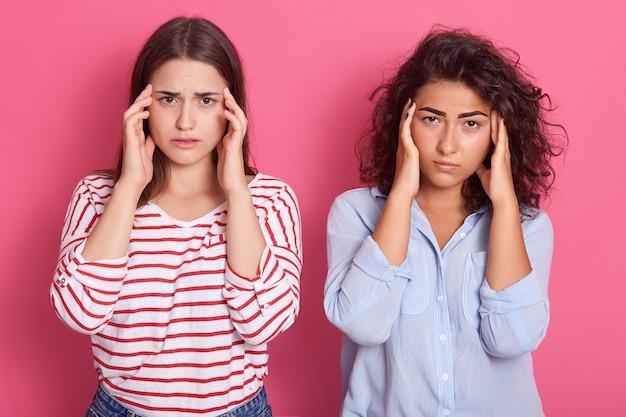 Tired dark haired women friends have headache