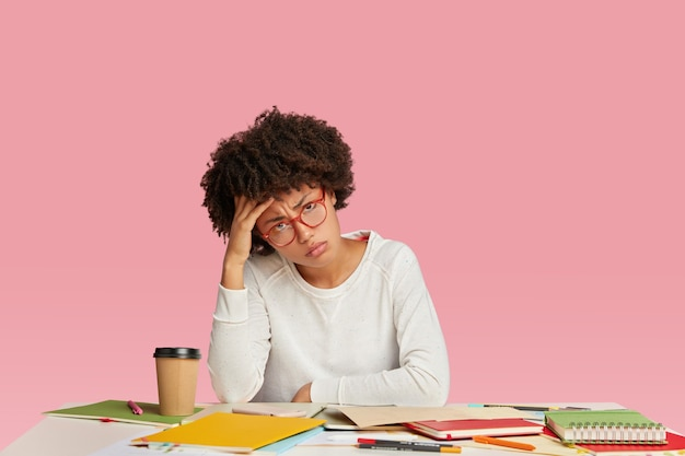 疲れた暗い肌のストレスのある実業家は、頭痛を感じ、疲労感を感じ、頭を抱え、白いカジュアルセーターを着ています