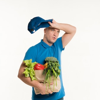 Tired delivery man posing with grocery bag