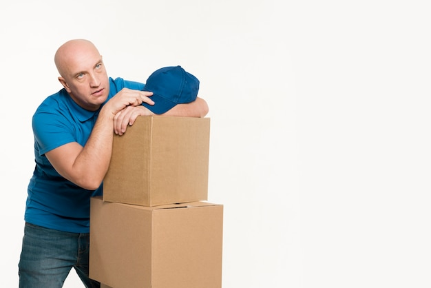 Tired delivery man resting on cardboard boxes and holding cap