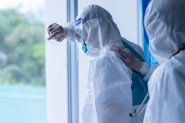 피곤한 우울한 의사 착용 ppe는 병원에서 코로나바이러스의 2차 확산으로 인해 의료 문제에 대한 필사적인 생각을 느낍니다