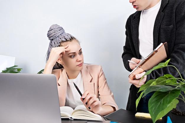 疲れた離れた若い女性は、男性の同僚が彼女のドキュメントとプロジェクトを見せている間、彼女の手がオフィスで働いているラップトップに座っている彼女の頭を支えます。頭痛、感情的な燃え尽き症候群、ストレス
