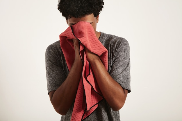 Tired disappointed young fit black athlete in gray shirt wiping sweat from his face with red waffle towel on white