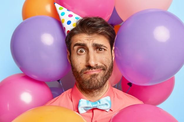Artista di intrattenimento dispiaciuto stanco alla festa per bambini, indossa un cappello di compleanno