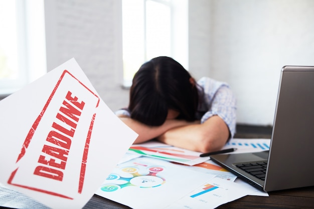 Tired disturbed female worker with headache.stressed woman in office holding head in hands and thinking about deadline