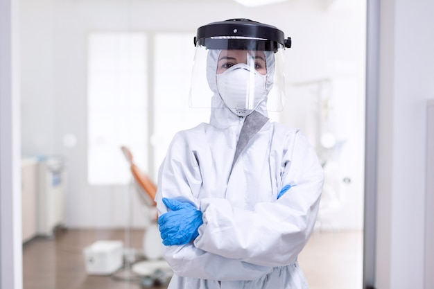 Tired doctor during global outbreak because of population infection with coronavirus. medical personal dressed in protection equipment against infection with covid-19 during global pandemic.