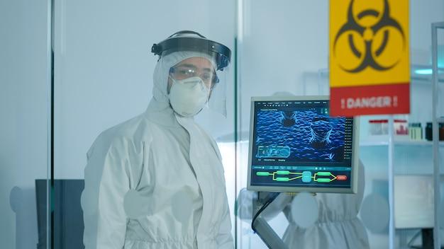 危険なエリアで働いているガラスの壁の後ろのカメラで疲れ果てているように見えるcovid-19に対する保護スーツの疲れた医者。科学研究のためにハイテクを使用してウイルスの進化を調べる科学者