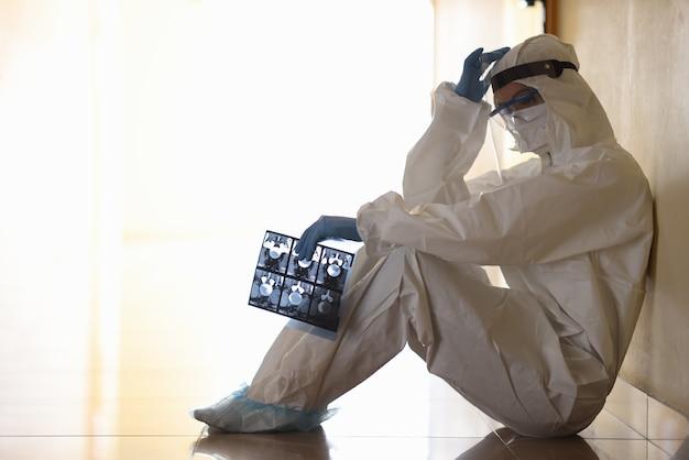 Усталый врач в защитном костюме, сидя на полу