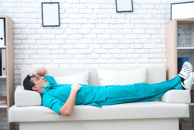A tired doctor is lying on the couch in his office.