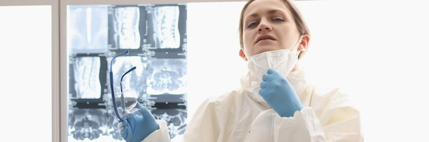 Tired doctor in protective suit sits on floor with xrays hanging in background