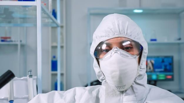 近代的な設備の整ったラボでカメラに疲れ果てているように見えるつなぎ服を着ている疲れた医者。科学研究、ワクチン開発のためのハイテクおよび化学ツールを使用してウイルスの進化を調べる科学者。