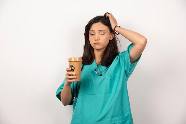 Medico stanco con una tazza di caffè che dorme su priorità bassa bianca. foto di alta qualità