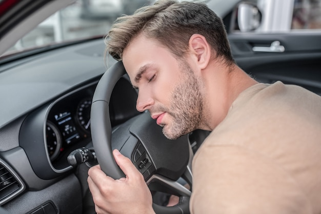 疲れたドライバー。車のハンドルに頭を乗せた軽いtシャツを着た居眠りしている男は日中疲れています