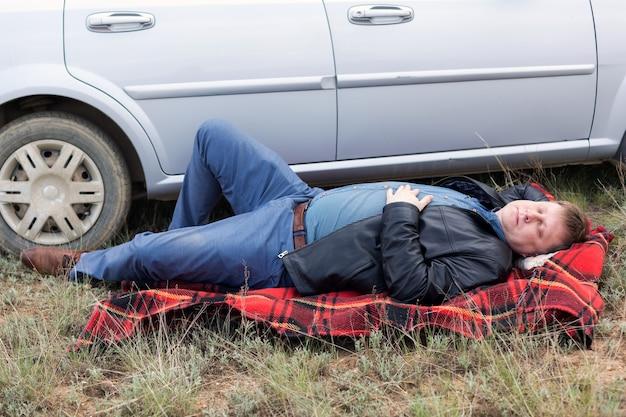 車の近くの地面で休んでいる疲れたドライバー。