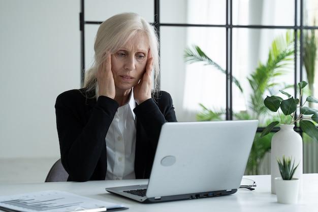 Усталая пожилая деловая женщина страдает от перенапряжения глаз после работы на ноутбуке в офисе