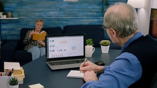 疲れた年配の起業家は、営業所で残業しているノートブックにノートパソコンの書き込みからグラフィックをチェックします。現代の技術ネットワークワイヤレス読書タイピング、検索を使用して忙しい従業員