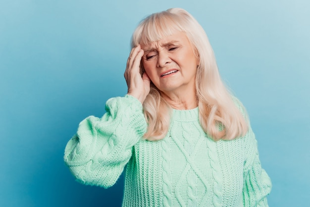 Tired elderly woman lady put hand head have headache isolated on blue background
