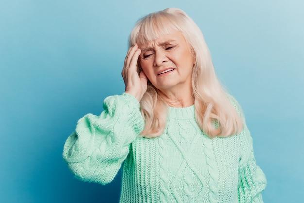 疲れた年配の女性の女性が手の頭を置く青い背景に頭痛が分離されている