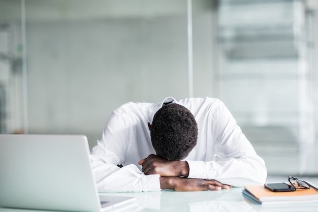 Tired employee in formal wear fall asleep after long working hours in office