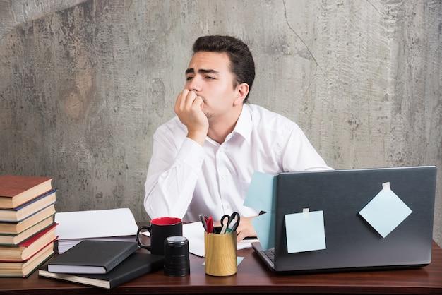 オフィスデスクで仕事を終えたいと思っている疲れた従業員。