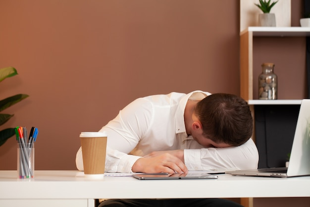 会社のオフィスのデスクで働いて疲れている従業員