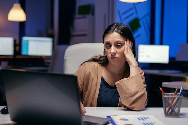 Усталый предприниматель пытается сосредоточиться на том, сколько работы нужно сделать к сроку. умная женщина, сидящая на своем рабочем месте в поздние ночные часы, делает свою работу.