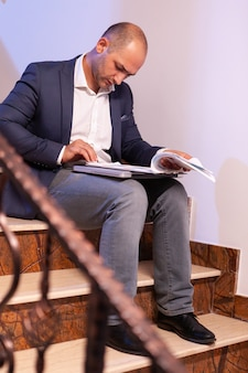 夜遅くの締め切り前に金融専門プロジェクトを完了するために過労をしている疲れた疲れたビジネスマン。夜遅くに働く起業家企業が建物の階段に座って