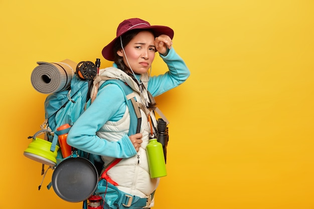Tired exhausted female tourist walks long distance on foot, looks with dissatisfaction at camera, stands sideways against yellow wall, carries backpack with personal stuff