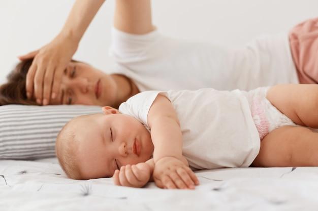 피곤한 지친 여성은 잠자는 아기 근처에 누워 있고, 손바닥을 이마에 대고, 아이와 누워 있고, 잠 못 이루는 밤을 보내고, 어머니가 됩니다.