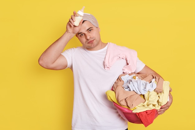 Tired exhausted husband who stands with baby items in isolated over yellow wall, father holds feeding bottle in hands, , keeps hand on her forehead.