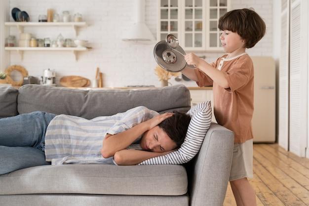 退屈な大声で息子と一緒にソファに横たわっている疲れた疲れ果てた母親のカバーの耳は、台所用品をゴロゴロと鳴らします