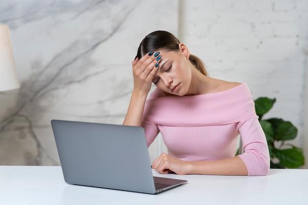 Усталая, истощенная, перегруженная работой, скучающая девушка, работающая онлайн за портативным компьютером, молодая красивая сонная девушка